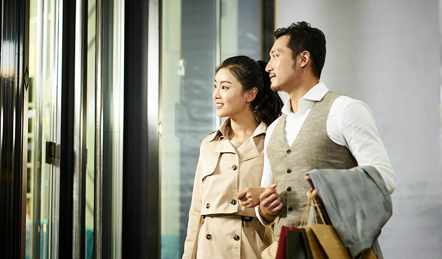A man and woman walking together with linked arms. The man is carrying shopping bags - Absolunet eCommerce Trends