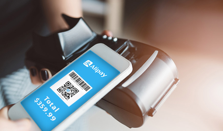 A mobile phone with a QR code and the Alipay logo being held up next to a receipt printer - Absolunet eCommerce Trends