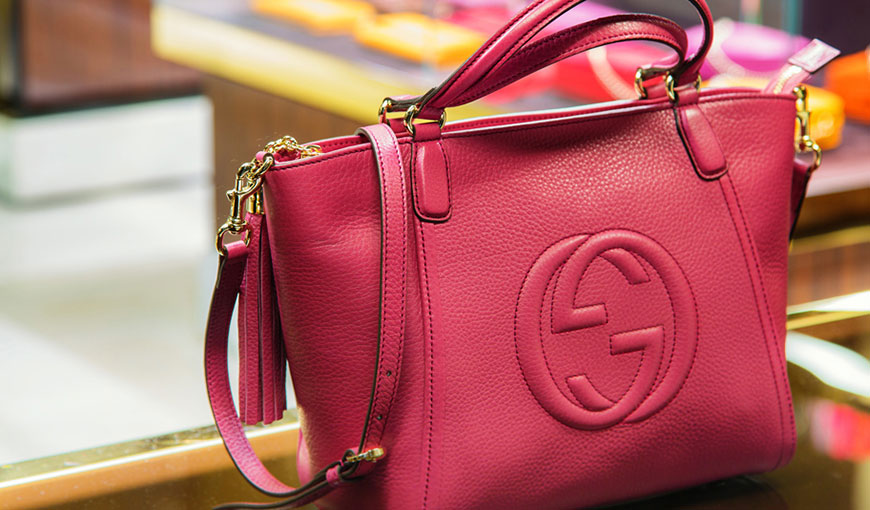 A pink purse with gold clasps and an upside down Gucci logo - Absolunet eCommerce Trends