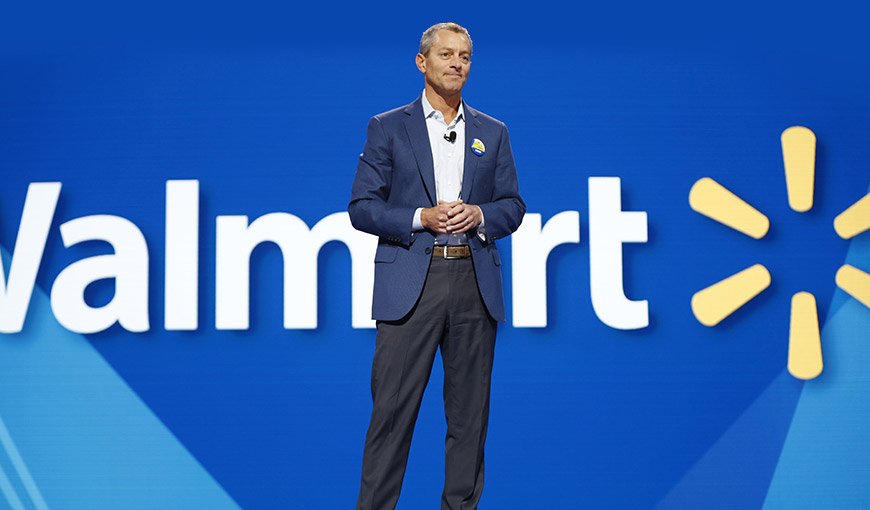 Man wearing a suit standing on stage with the Walmart logo behind him - Absolunet eCommerce Trends