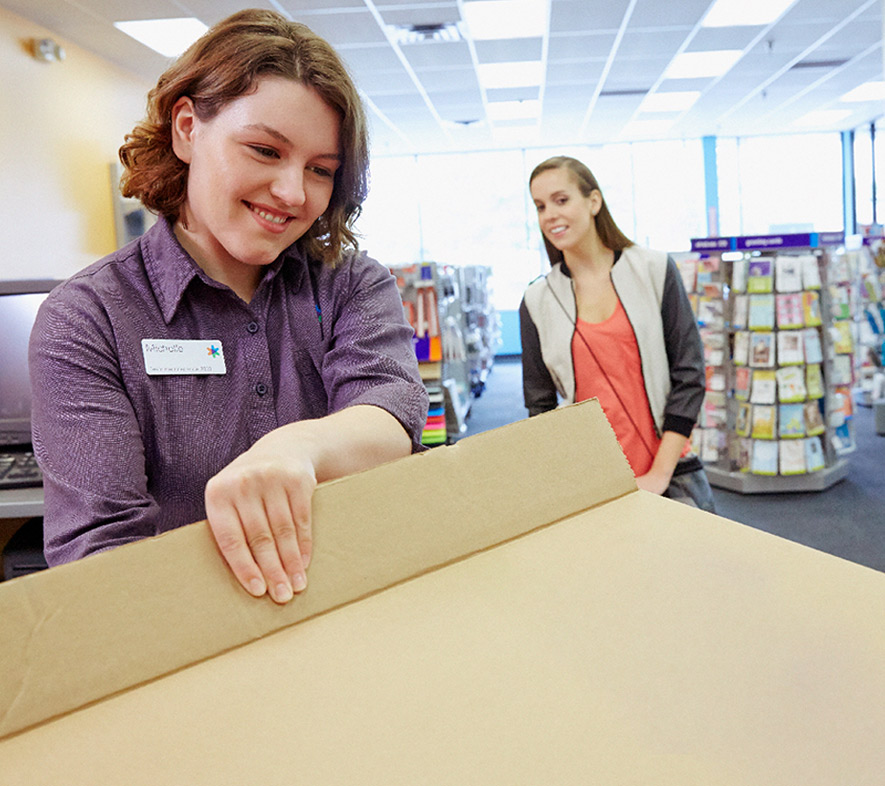 A closeup of a delivery person handing a box to another person - Absolunet eCommerce Trends